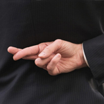 Dishonest businessman with fingers crossed behin back