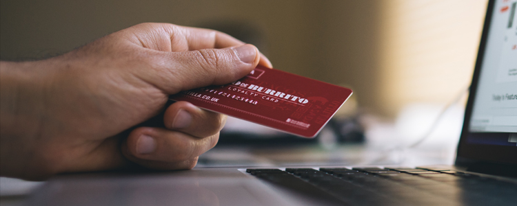 Hand holding a credit card in front of a laptop computer