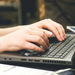 Photo of a person typing on a laptop keyboard